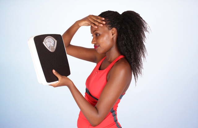 Frustrated-woman-looking-at-weight-scale